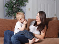Mother and young son laughing and playing pretty her toddler horseplaying on couch at home in living room together while bonding Stock Image