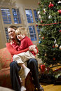 Mother and young son sitting by Christmas tree Stock Images
