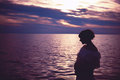 Motherhood and sunset pregnant woman standing in the sea at Royalty Free Stock Photo