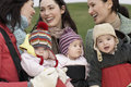 Mothers with babies in slings at park cheerful young chatting outdoors Royalty Free Stock Image