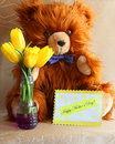 Mothers day card teddy bear gift stock photo with flower bouquet of yellow tulips and greeting with happy mother s text Stock Photos