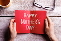 Mothers day composition. Hands of mom holding greeting card Royalty Free Stock Photo