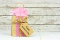 Mothers Day gift bag with tag against rustic white wood Royalty Free Stock Photo