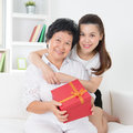Mothers day gift senior women receiving a from adult daughter beautiful asian family at home Royalty Free Stock Photos