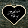 Mothers day a heart shaped blackboard with the text written in it on an old wooden surface Royalty Free Stock Photos