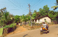 Motion blur from motorbike with tourists driving on village in popular Goa state, India. Rural landscape. Royalty Free Stock Photo