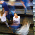 Motion blur of woman standing in busy school Stock Photos