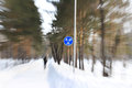 Motion blur zoom photo of running man in winter the park bike lane road sign Stock Photo