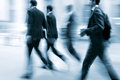 Motion blurred business people walking on the street at rush hour in in style of blur and blue tonality Royalty Free Stock Photo