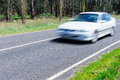 Motion blurred car driving along a quiet country road. Royalty Free Stock Photo