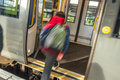 Motion blurred teen boy entering train door Royalty Free Stock Photo