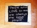 Motivational proverb people who love to eat are always the best people interpretation handwritten on blackboard over beige wooden Stock Image