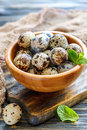 Motley quail eggs in a wooden bowl.