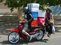 A motobike driver with a passenger carries boxes Royalty Free Stock Image