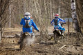 Motocross chase two motorbikes riding in race on muddy terrain in parola finland Stock Images