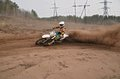 Motocross practice racer at turn of in sandy ruts mx the rider the reversal on the with a large plume Royalty Free Stock Photos