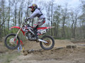 Motocross Racer Jumping Over a Small Hill Stock Image