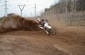 Motocross racer moves along sandy parapet turning track per motorcycle large plume of sand Stock Image