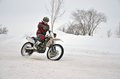 Motocross on snow, the driver manages motorcycle one arm on snow Stock Photography