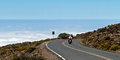 Motor cyclist above the clouds biker cruising down towards and pacific ocean in distance on steep road to and from ft high Royalty Free Stock Photography