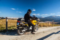 Motorbike traveler in mountains rider having black wear and helmet during travel Royalty Free Stock Photo