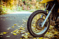 Motorbike wheel and tire detailed view of front with autumn road in background Stock Photography