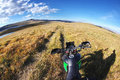 Motorcycle enduro traveler with suitcases standing on a wide orange sunset dawn mountain meadow plateau