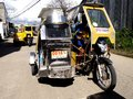 A motorcycle fitted with additional wheels and a cab is turned into what is called a tricycle samar philippines november means Royalty Free Stock Photos