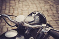 Motorcycle handlebar a of an oldtimer with brownshaded cobblestone pavement in the background Stock Images
