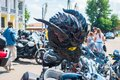A motorcycle helmet with a devil face hangs on the handlebars of a motorcycle Royalty Free Stock Photo