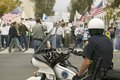 A motorcycle policeman looks at protesters against george w bush and the iraq war at an anti iraq war protest march in santa barb Stock Photo