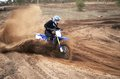 Motorcycle rider bogged down in loose sand cornering on a steep bend motocross track Royalty Free Stock Photo