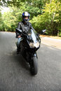 Motorcyclist goes on road, front view Stock Photos