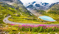 Motorcyclist on mountain pass road in the Alps Royalty Free Stock Photo