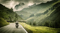 Motorcyclist on mountainous highway cold overcast weather europe austria alps extreme sport active lifestyle adventure touring Royalty Free Stock Images