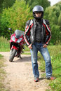 Motorcyclist standing on country road near bike Stock Images