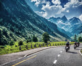 Motorcyclists on mountainous road enjoying tour along alps summertime activities wonderful mountain landscape extreme vacation Royalty Free Stock Image