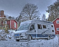 Motorhome in snow and hdr camper parked mountain car park an old red wooden house the countryside winter whid Stock Photography