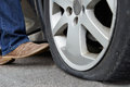 Motorist Kicking Flat Tyre On Car Royalty Free Stock Photo
