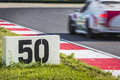Motorsports stone slab next to the curb stones on a race track indicates the breaking point for a passing race car approaching the Royalty Free Stock Image