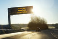 Motorway gantry sign in winter early morning sunshine reading caution freezing conditions Stock Photos