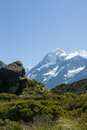 Mount cook ahead beyond the lush green valley and rock outcrops on hooker track in aoraki national park south Stock Photo