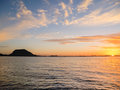 Mount maunganui silhouetted on horizon as a golden sunrises Stock Image