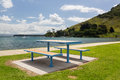 The mount at tauranga in nz bay and harbour with picnic table on sandy beach by calm water front of Stock Photos