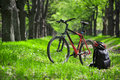 Mountain bike, backpack and helmet on a trail in the forest Royalty Free Stock Photo
