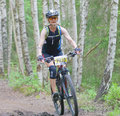 Mountain bike woman cycling downhill in the birch forest Royalty Free Stock Photo