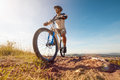 Mountain biker in action across rocks against blue sky concept for healthy lifestyle excercise and extreme sports Royalty Free Stock Photography