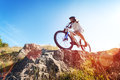 Mountain biker in action across rocks against blue sky concept for healthy lifestyle exercise and extreme sports Royalty Free Stock Images