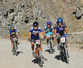 Mountain bikers uphill on rural road in rocks Royalty Free Stock Image