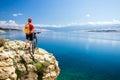 Mountain biking rider looking at inspiring sea and mountains Royalty Free Stock Photo